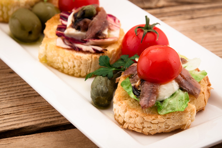 anchovy fish: Crostini vith mozzarella cheese anchowy and tomato on wooden board