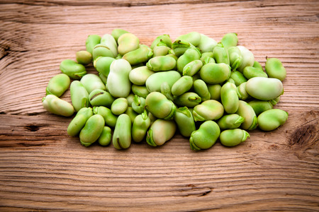 broad: Fresh broad bean on old wooden background close up Stock Photo