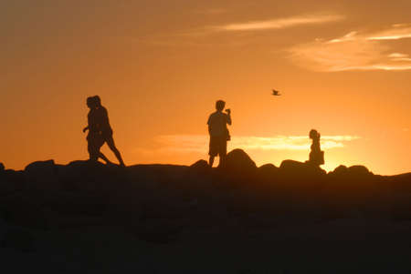 Romantic couples taking pictures and walking at sunset photo