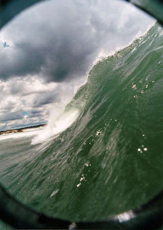 Wave breaking with buildings in the background photo