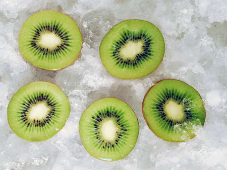 Upper view of five halves fresh fruit on ice cubes. Cut kiwis on ice background photo