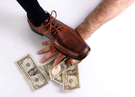 treading: Brown shoe treading a hand trying to get money. Concept of power, force, big brother.