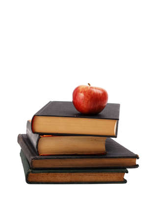 Ripe red apple on a book pile. Isolated on white background photo