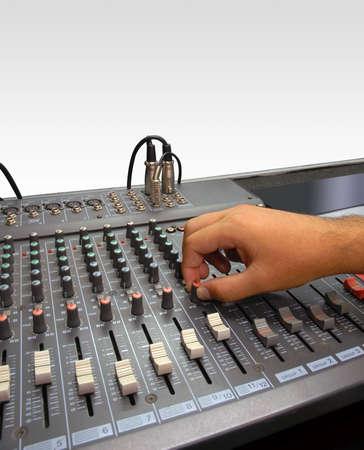 Consola de mezclador de sonido de un estudio de grabaci�n. Mano de un hombre que hacer ajustes con una perilla de control. Fondo blanco  Foto de archivo - 5652429
