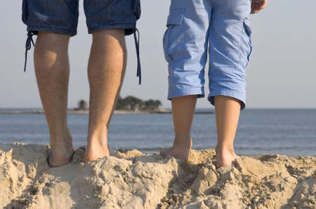 Legs of father and son at the top of a sand dune, walking towards the sea photo