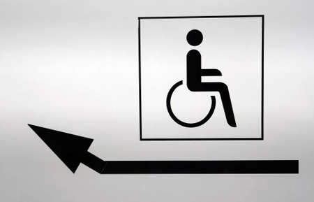Disabled icon with an arrow pointing to the left. White wall painted on black Stock Photo - 5683985