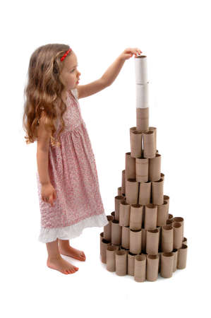 Little girl making a Christmas Tree with cardboard rolls of toilet paper photo