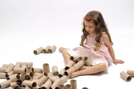 Little girl playing with lots of cardboard toilet paper rolls. White background photo