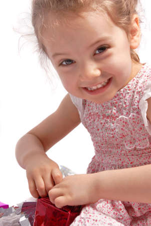 Little girl with a Christmas present smiling and looking at the camera. White background photo