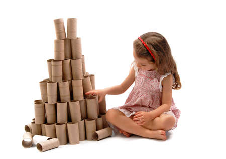 Little girl making a Christmas Tree with cardboard rolls of toilet paper. White background photo
