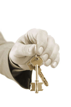Close-up of a male real estate executive's hand holding two keys. Warm tones picture. Stock Photo - 5847569