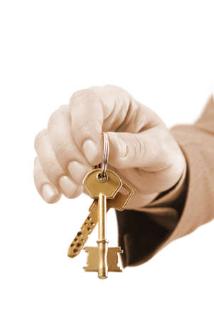 Close-up of a male real estate executives hand holding two keys. Warm tones picture. photo