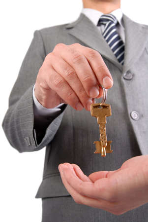 Businessman handing a key to success over a woman palm isolated on white. Stock Photo - 5847573