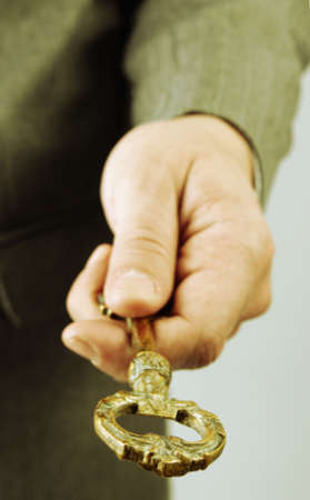 Businessman handing and giving a key to success. Warm tones picture. Stock Photo - 6244056