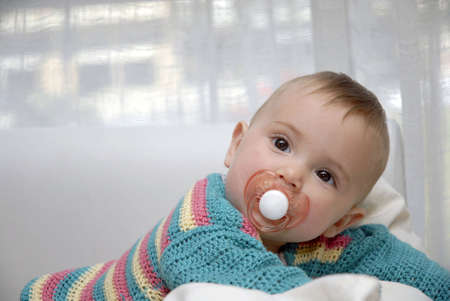 Portrait of a baby girl with pacifier. photo