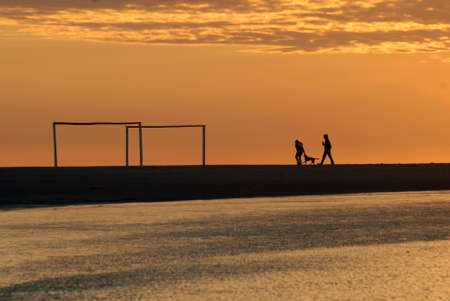 arcs: Beautiful golden sunrise seascape with soccer arcs and a running couple in the background. Montevideo, Uruguay
