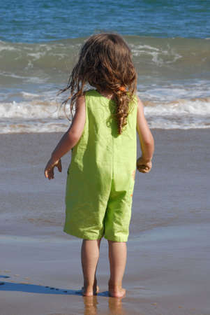 contemplates: Little girl contemplates the ocean, with expectation for the wave to wet her feet Stock Photo