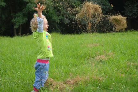 ni�os jugando en el parque: Chica de Blondie jugando con hierba en el campo verde.