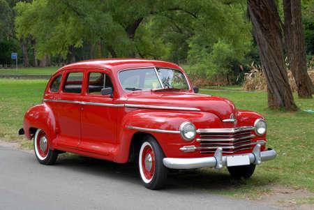 Antieke rode auto tegen een achtergrond van groene bomen  Stockfoto