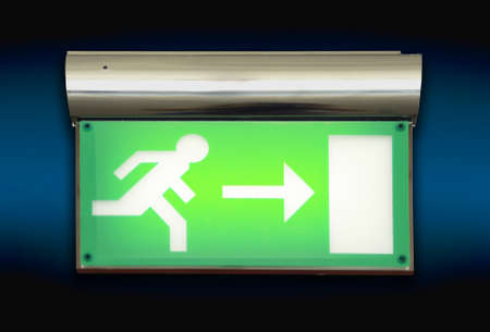 Emergency blinking exit sign over blue background photo