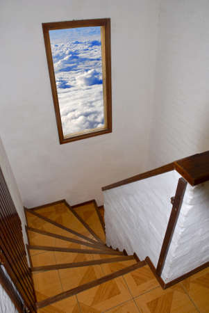 Staircase with open window to a cloudy sky photo