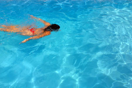 Girl swimming underwater in a clear water swimming pool photo