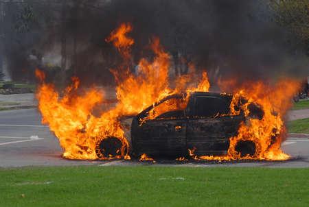 quemadura: Coche en llamas en una calle de la ciudad