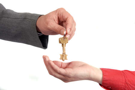 Businessman handing a key to success over a woman palm. Stock Photo - 9767331