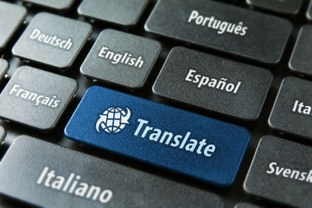 spanish language: Multilingual translation online concept. Close up of multi language keyboard and translate word key in blue color with clippingpath. Stock Photo