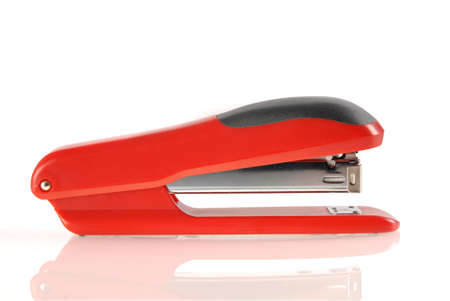 A red and black stapler isolated with reflection on white background. Included clipping path, so you can easily cut it out and place over the top of a design. photo