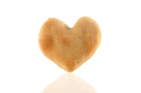 Single Heart-shaped cookie isolated with reflection on white background. Included clipping path, so you can easily cut it out and place over the top of a design. photo