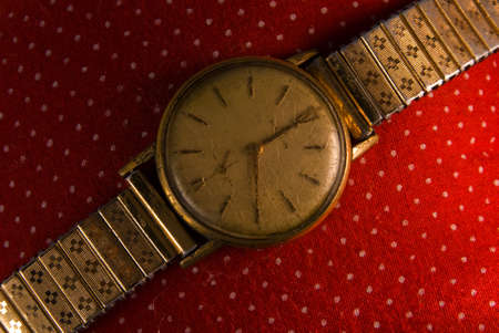 Retro golden wristwatch close up on red vintage cloth background. photo