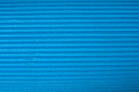 Vintage cyan corrugated cardboard macro close up. Useful as background for design works. photo