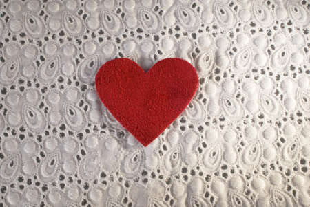 Retro Love. White fabric and red heart shape conceptual composition. Macro texture close up useful as background for design works. photo