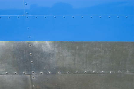Airplane fuselage blue and silvel metal texture with rivets  Useful as background for design works  photo