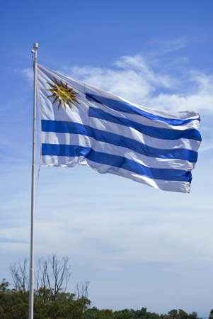 Uruguay flag flames over a blue clear sky background. photo