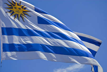 Uruguay flag flames close-up over a clear blue sky background. photo