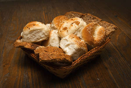 Delicious bread arrangement in basket on wooden table photo