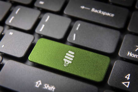 green computing: Green energy key with eco bulb light icon on laptop keyboard. Included , so you can easily edit it. Stock Photo