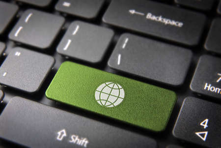 teleworker: Global go green key with Earth icon on laptop keyboard. Included , so you can easily edit it. Stock Photo