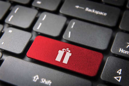 teleworker: Red Christmas key with gift box icon on laptop keyboard.