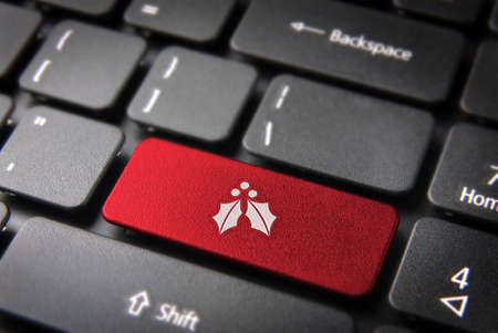 computer key: Red Christmas key with mistletoe icon on laptop keyboard.