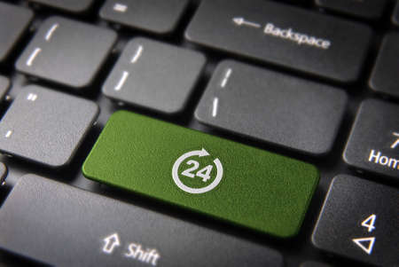 always: Online business always open concept: green key with 24 working hours symbol on laptop keyboard.