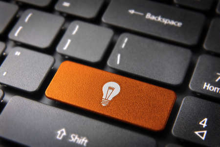 creative power: Internet business new ideas concept: orange key with bulb lamp icon on laptop keyboard. Stock Photo