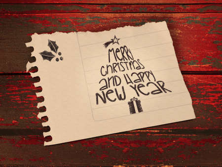Vintage Merry Christmas and happy new year message in paper note over wooden background.  photo