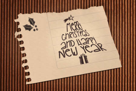 Vintage Merry Christmas and happy new year paper note over corrugated cardboard background.  photo