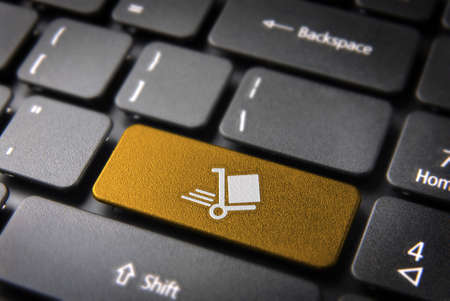 teleworker: Delivery key with shipping cart icon on laptop keyboard. Included clipping path, so you can easily edit it.