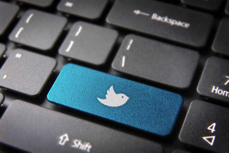 teleworker: Socialmedia key with twitter bird icon on laptop keyboard. Included clipping path, so you can easily edit it.
