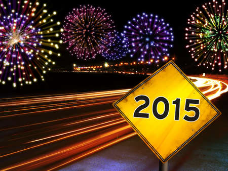 newyear night: Happy New Year 2015 fireworks and city cars highway lights with yellow road sign.
