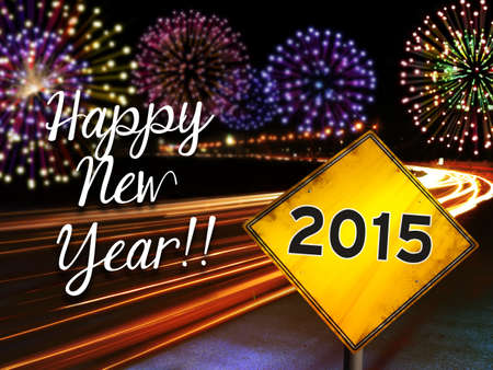 Happy New Year 2015 fireworks and city cars highway lights with yellow road sign.  photo